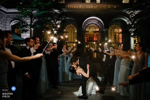 The groom kisses his bride as guests hold sparklers on either side of them in this photo by a Manhattan, NY wedding photographer.