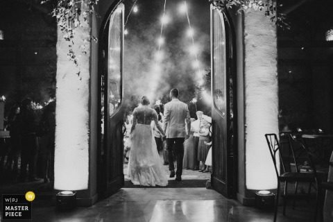 Black and white photo of the bride and groom exiting as they hold hands, taken from behind by a San Antonio, TX wedding photographer.