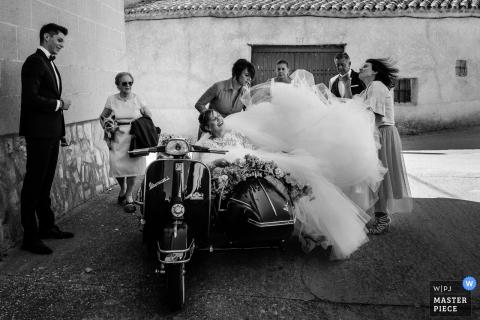 Zwart-witte foto van de bruid die in de zijauto van een motorfiets zitten aangezien de gasten met haar toga door een het huwelijksfotograaf van Leon proberen te helpen.