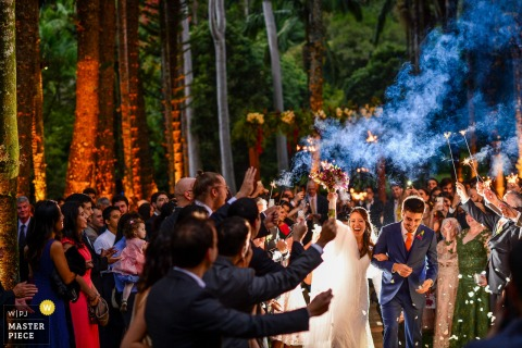 Photo of the bride and groom exiting the outdoor ceremony through guests holding sparklers and throwing petals by a São Paulo, Brazil wedding photographer.