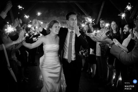 Zwart-witte foto van de bruid en de bruidegom die tussen gasten lopen die sterretjes houden door een het huwelijksfotograaf van Boston, doctorandus in de letteren.
