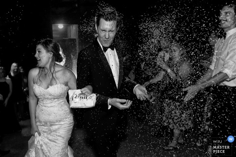 A Lake Tahoe, California wedding photo of a bride and groom walking towards the camera as rice is thrown at them