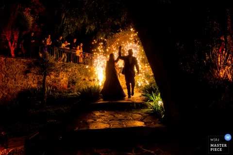 Wedding picture of a bride and groom walking down a dark path towards the camera in San Diego, California