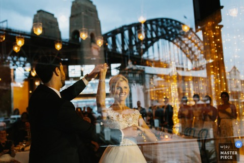 Photo of the bride and groom taken through a window with the reflection of a bridge by a New South Whales, Australia wedding photographer.
