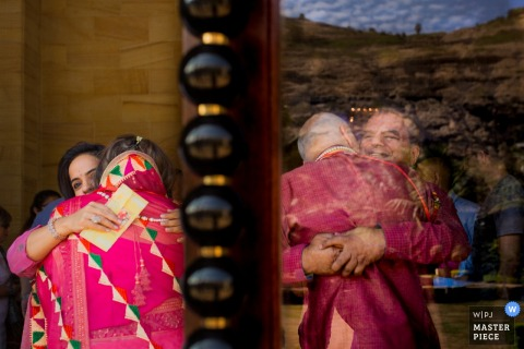 Two women hug next to the reflection of two men hugging in this photo by a Gujarat, India wedding photographer.