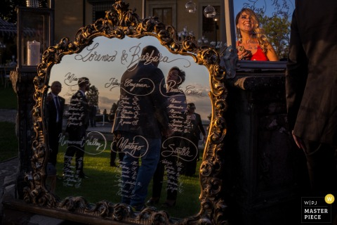 Guests are reflected in an ornate mirror with writing on it in this photo by a Florence wedding photographer.