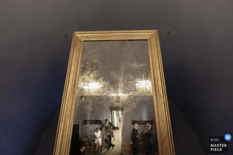 En esta foto, un fotógrafo de bodas de Lombardía refleja a los invitados en un gran espejo a lo largo del piso.