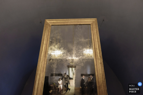Guests are reflected in a large, floor-length mirror in this photo by a Lombardy wedding photographer.