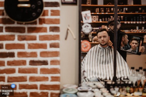 A barber holds up a mirror for the groom in this photo taken from outside by a Centre-Val de Loire wedding photographer.