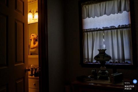 La mariée épouse son maquillage dans la salle de bain, visible dans le miroir, à travers une fente de la porte de la salle de bain sur cette photo prise par un photographe de mariage de San Diego, Californie.
