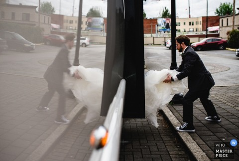 El novio ayuda a la novia con su vestido mientras se sube a un autobús en esta foto de un fotógrafo de bodas de Columbia Británica, Canadá.