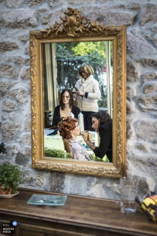 Photo of two women getting their hair and makeup done reflected in a mirror in a wall. Taken by a Playas de la Loire wedding photographer.