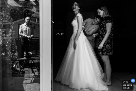 Black and white photo of two women helping the bride with her dress while a man is reflected in the window by a Rotterdam wedding photographer.