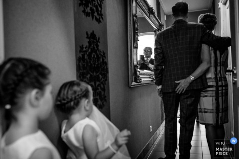 Black and white photo of two young girls watching a couple walk down a hallway by a Netherlands wedding photographer.