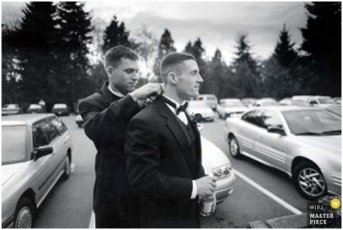 Black-and-white photograph of the groom receiving help with his tie and tuxedo in the parking lot