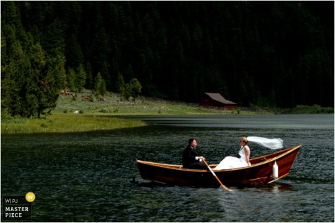 The bride and groom paddle a rowboat on the lake