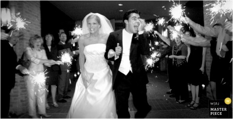 The bride and groom depart from their reception to a gauntlet of guests with sparklers