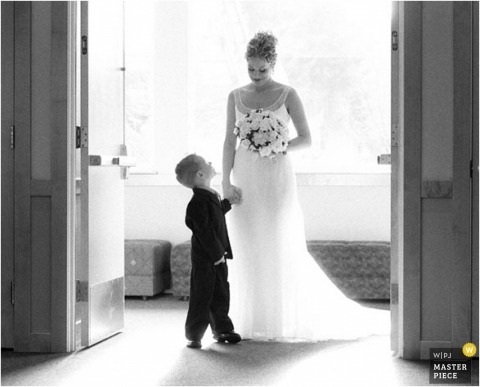 The bride holds her bouquet and the hand of a young ring bearer in this black-and-white photo