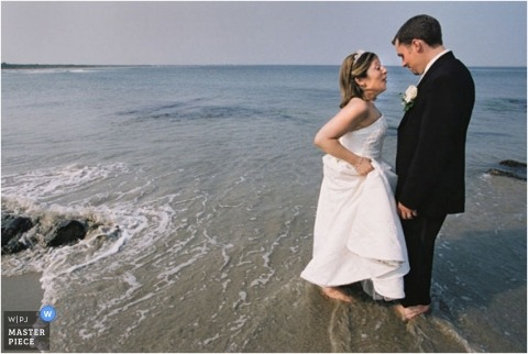 The bride and groom take their shoes off and wade into the ocean in gown and tuxedo