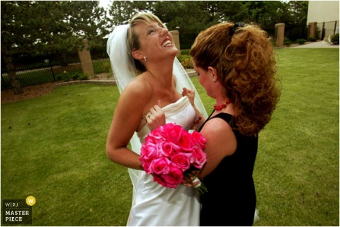 A friend helps the bride pull her dress up on the grassy lawn