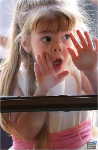 Humorous image of a fun flower girl smashing her face against window glass