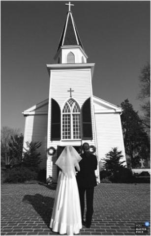Verticale zwart-wit foto van de bruid op het punt om de kerk binnen te gaan