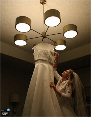 The bride retrieves her dress hanging from an art deco chandelier
