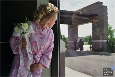 The bride holds her bouquet and looks out the window at arriving guests