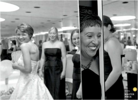 Baltimore mother of the bride looks from behind mirrors at the bride in her dress