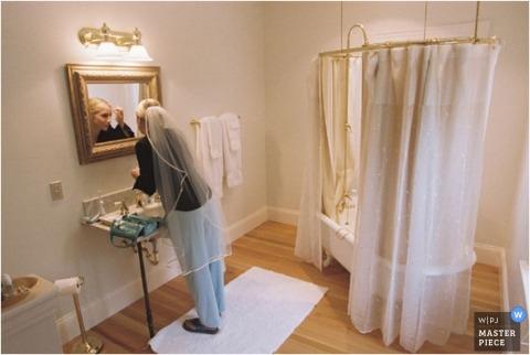 Atlanta bride prepares for make up in the bathroom mirror by herself