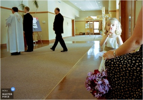 The flower girl understands it is time to be quiet during the ceremony