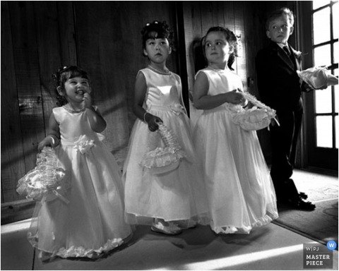 The ring bearer in flower girls lined up as they prepare to enter the church for the wedding ceremony