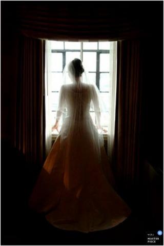 Vertikales Foto der Braut, die heraus sie erhält bereites Raumfenster schaut