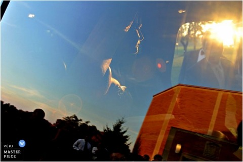 sunset glass reflection photo of bride and groom