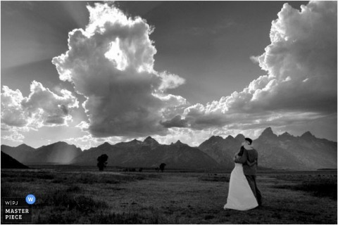 photo of bride and groom under dramatic clouds in the mountains