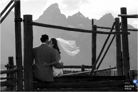 Bride and groom kissing with mountain view on wedding day.