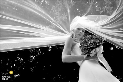 Creative portrait of the bride under her veil in black-and-white