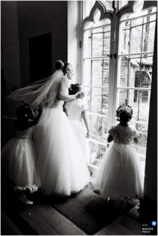 Bride and flower girls look out the window before the Maryland ceremony.
