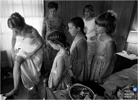 ATL-Braut zieht Strumpfband an, während Blumenmädchen zusehen