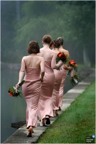 Color photo of bridesmaids walking in single line along grass and water.