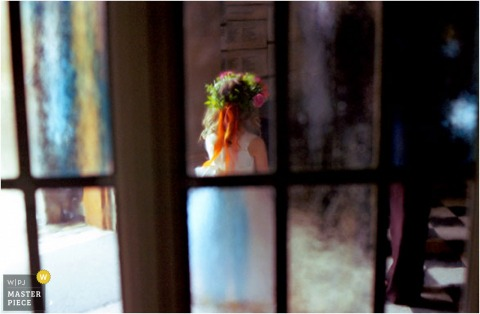 Photo of flower girl through glass panes.