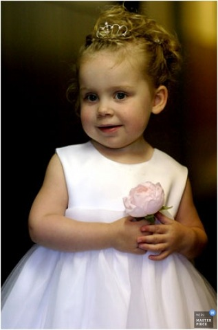 cute flower girl holding single flower