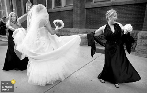 Two bridesmaids help the bride with her dress while walking on the sidewalk