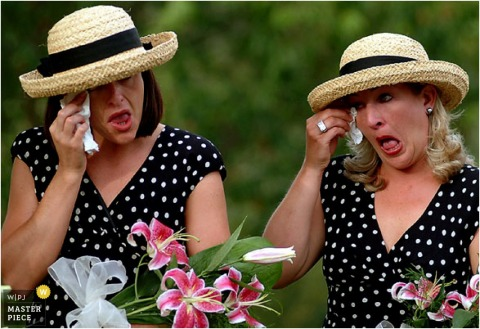 Two bridesmaids wipe tears at the same time during wedding ceremony