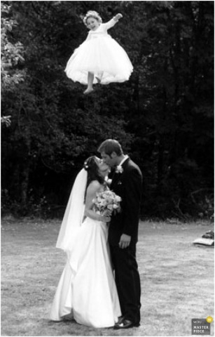 flower girl tossed in the air behind bride and groom