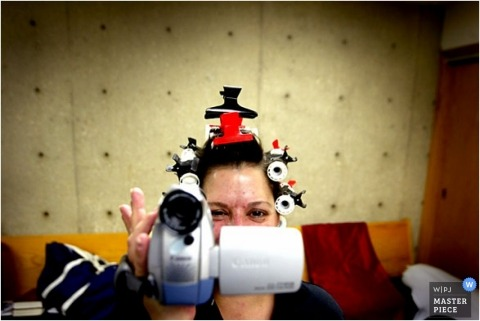 Bride with curlers hair clips and video camera while getting ready for her wedding