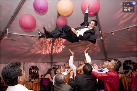 Colorado wedding tent image of the groom being thrown into the air