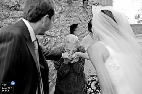 Fotografía de bodas en Italia | La novia y el novio reciben un beso en las manos de un abuelo