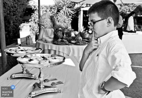 Italian Wedding Reception Photo of a boy contemplating over the desserts