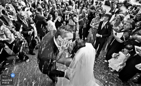 Wedding Photographer Roma, Italy | The bride and groom are showered with rice from their many guests